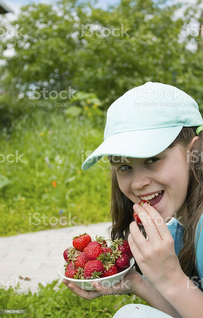 Little girl eats ripe strawberry royalty-free stock photo