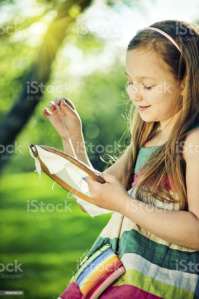 Little girl embroidering outdoors royalty-free stock photo