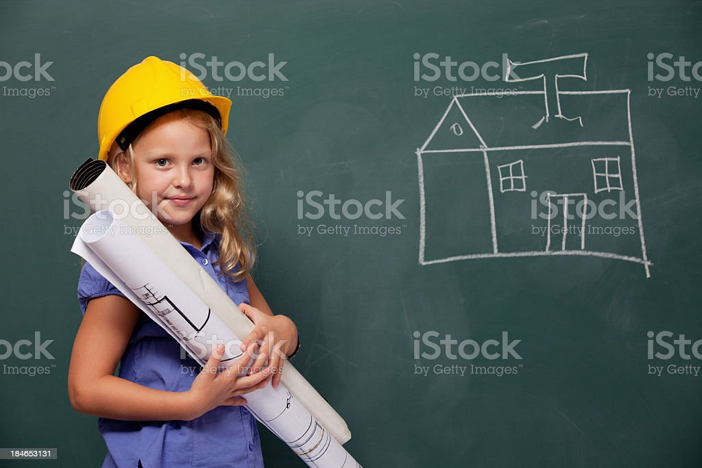 Little Girl Engineer With Protective Helmet Holding Blueprints royalty-free stock photo