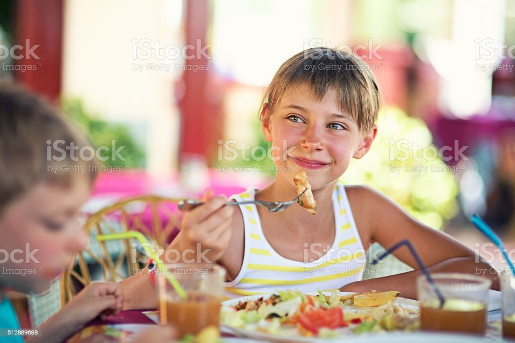 Little girl enjoying dinner in restaurant with family stock photo