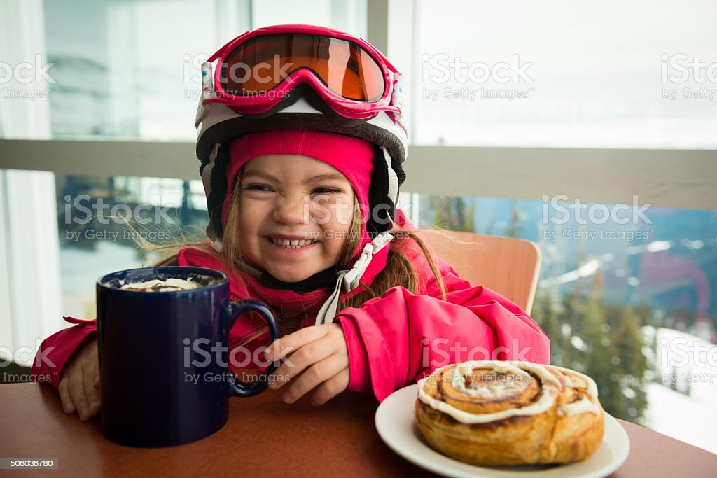 Little girl enjoying hot chocolate after skiing stock photo