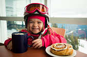 Little girl enjoying hot chocolate after skiing