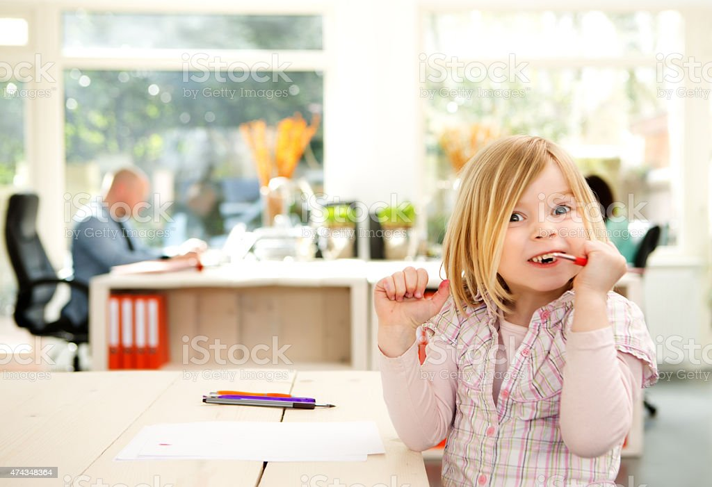little girl entertaining herself while parents working stock photo