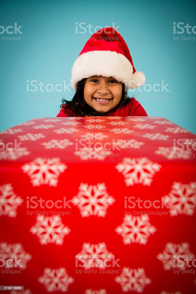 Little Girl Excited About Receiving/Giving a Christmas Present stock photo