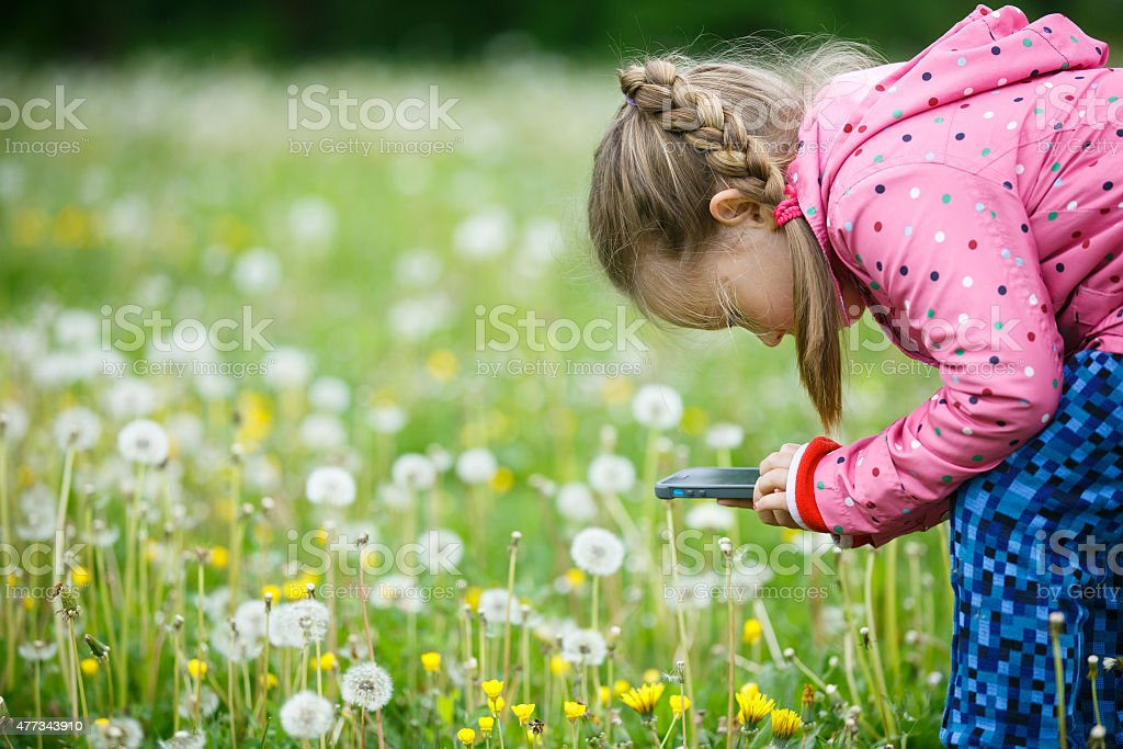 Little girl exploring nature with her smart phone stock photo