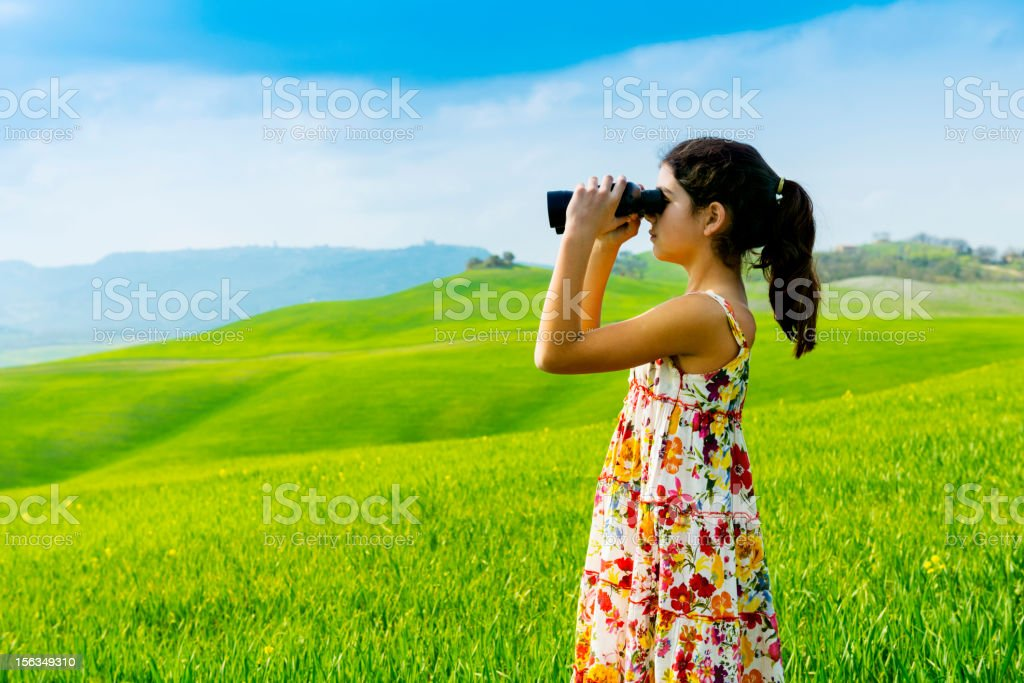 Little girl exploring with binoculars in Tuscany - Italy royalty-free stock photo