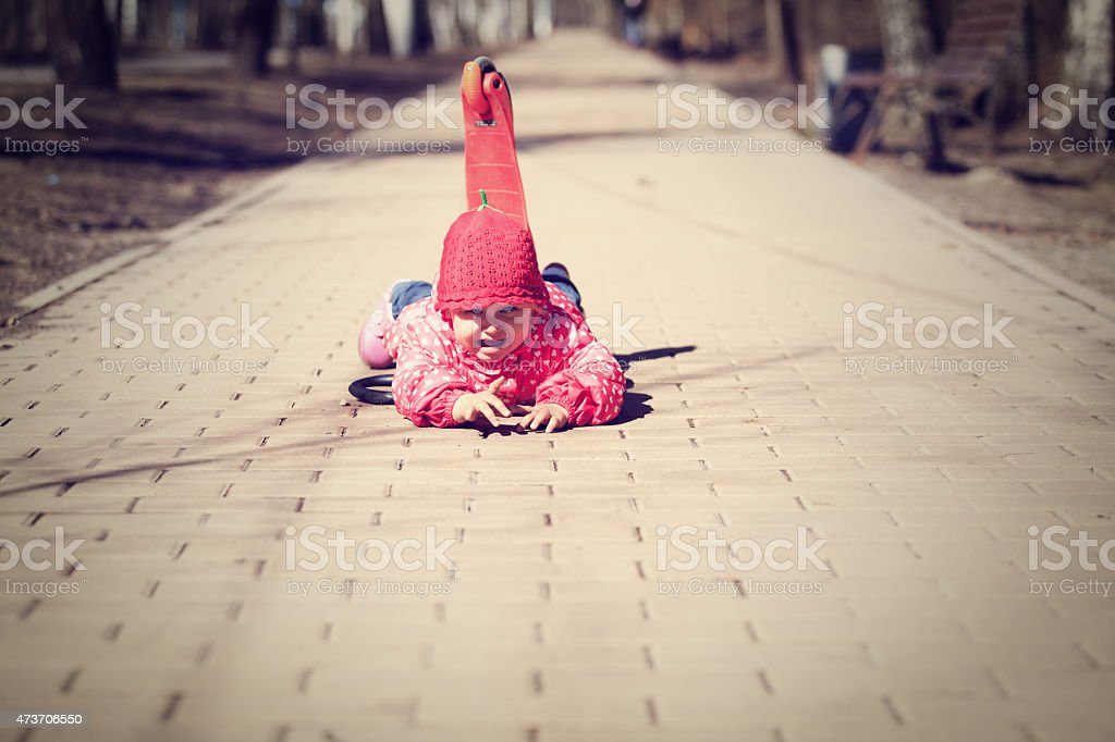 little girl fall off of scooter stock photo