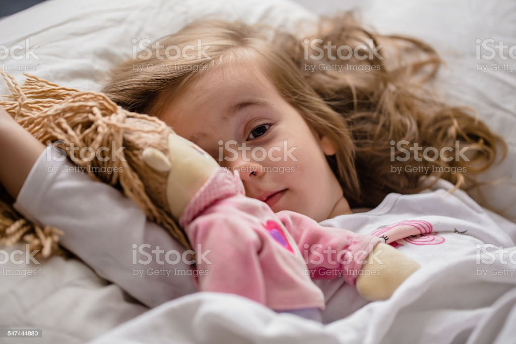 little girl falls asleep in bed with soft doll white stock photo