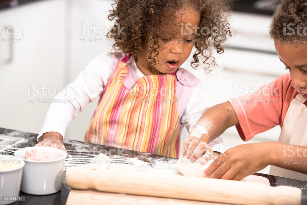 Little Girl Fascinated By Her Brother Preparing Dough stock photo