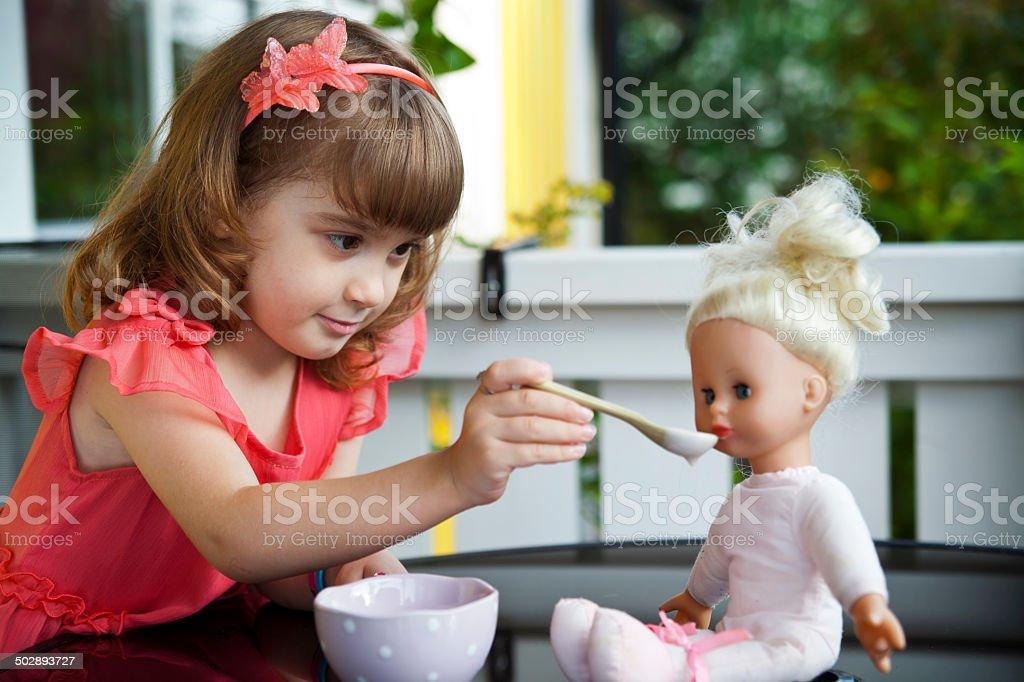Little girl feeding a doll stock photo