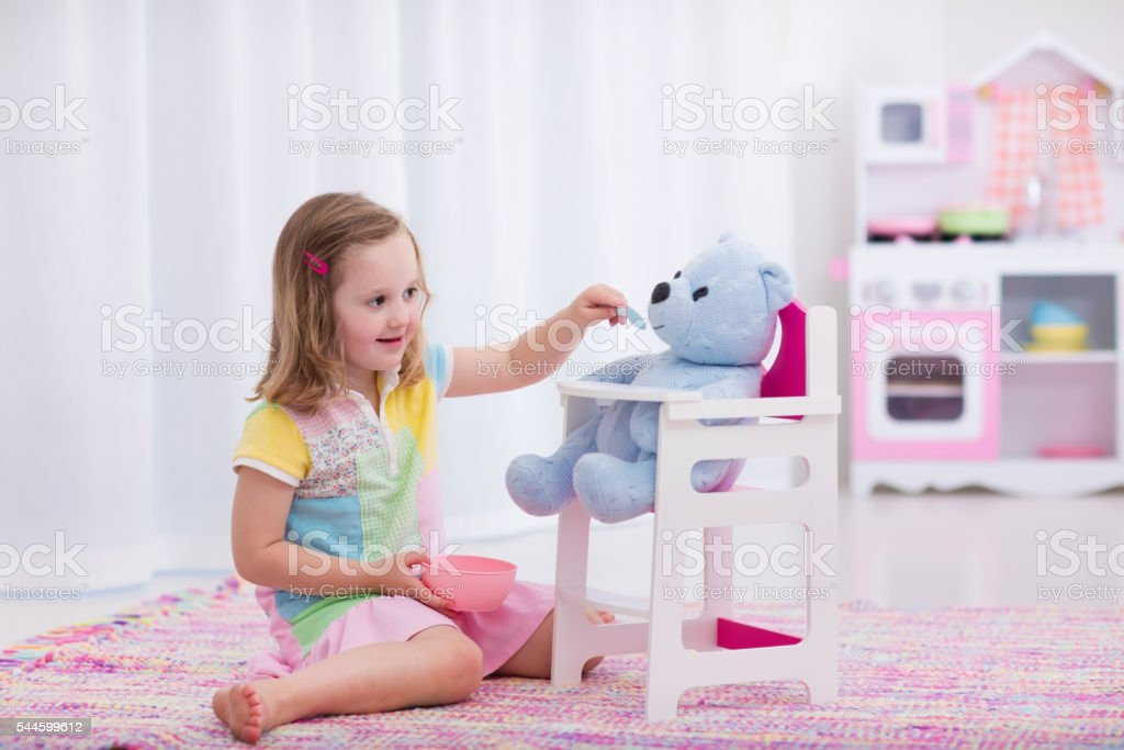 Little girl feeding her toy teddy bear stock photo