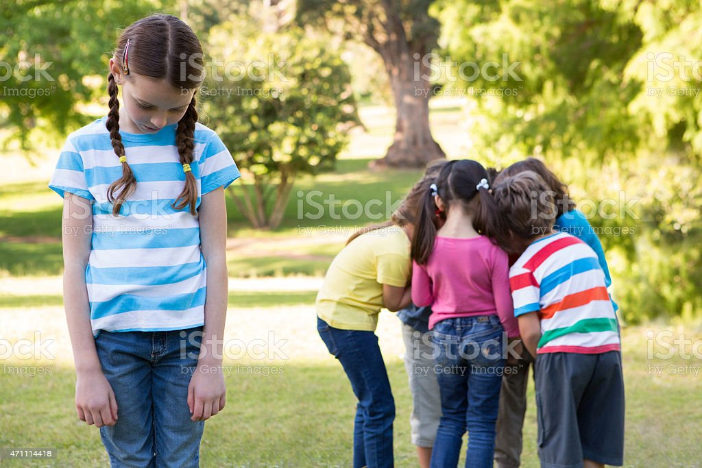 Little girl feeling left out in park stock photo