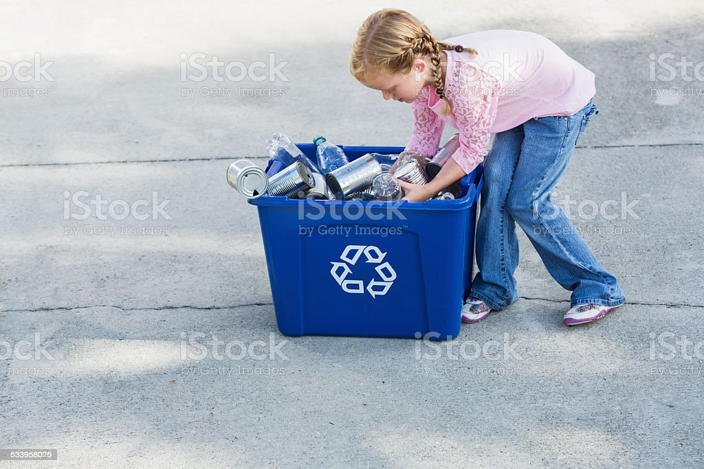 Little girl filling recycling bin with cans and bottles stock photo
