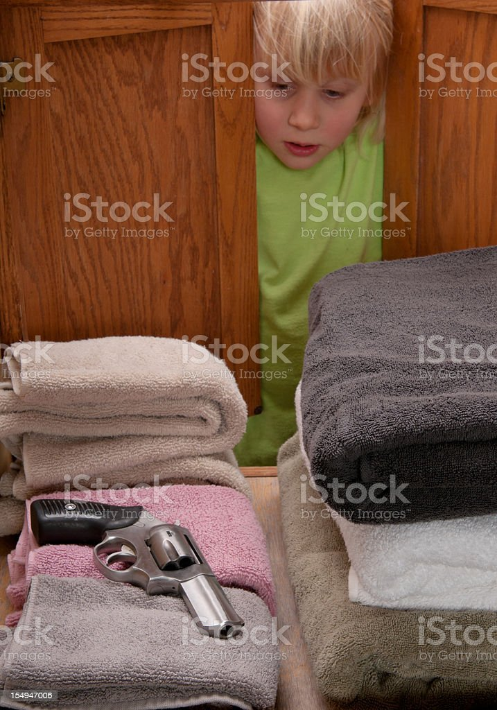 CHILD SAFETY SERIES-#5 little girl finding a gun stock photo
