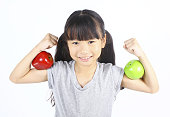Little girl flexes her muscle with two apples