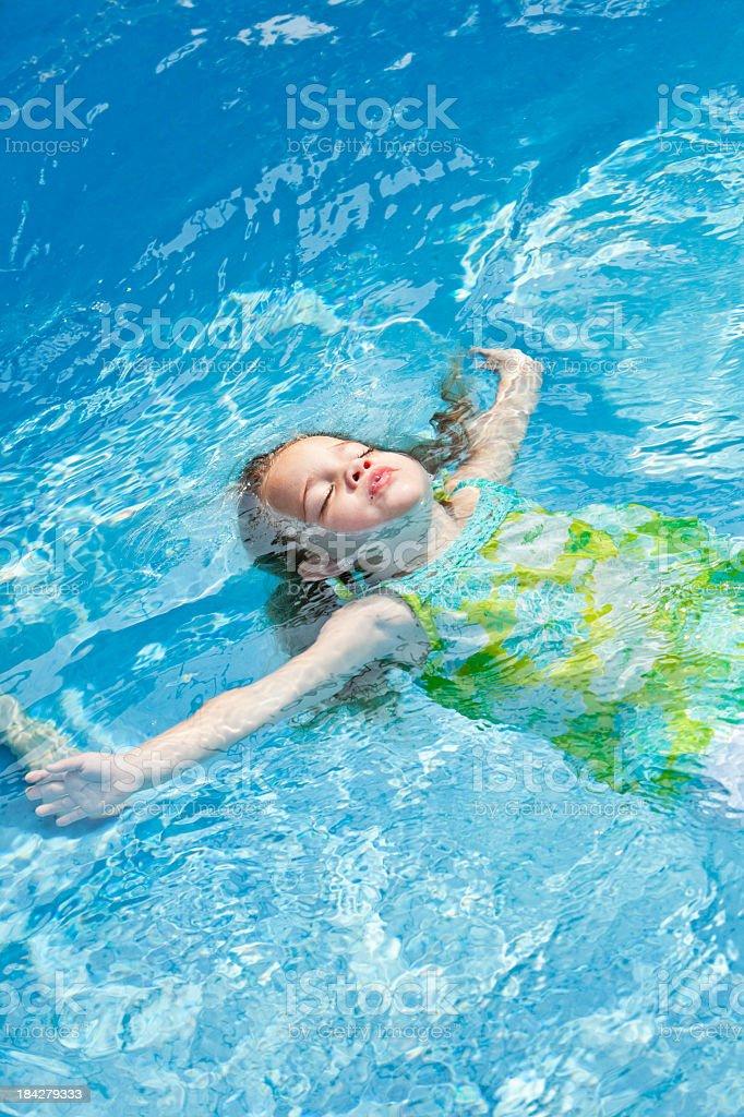 Little girl floating on back stock photo