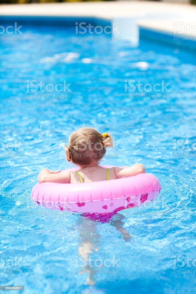 Little Girl Floating With Swim Ring in Outdoor Pool royalty-free stock photo