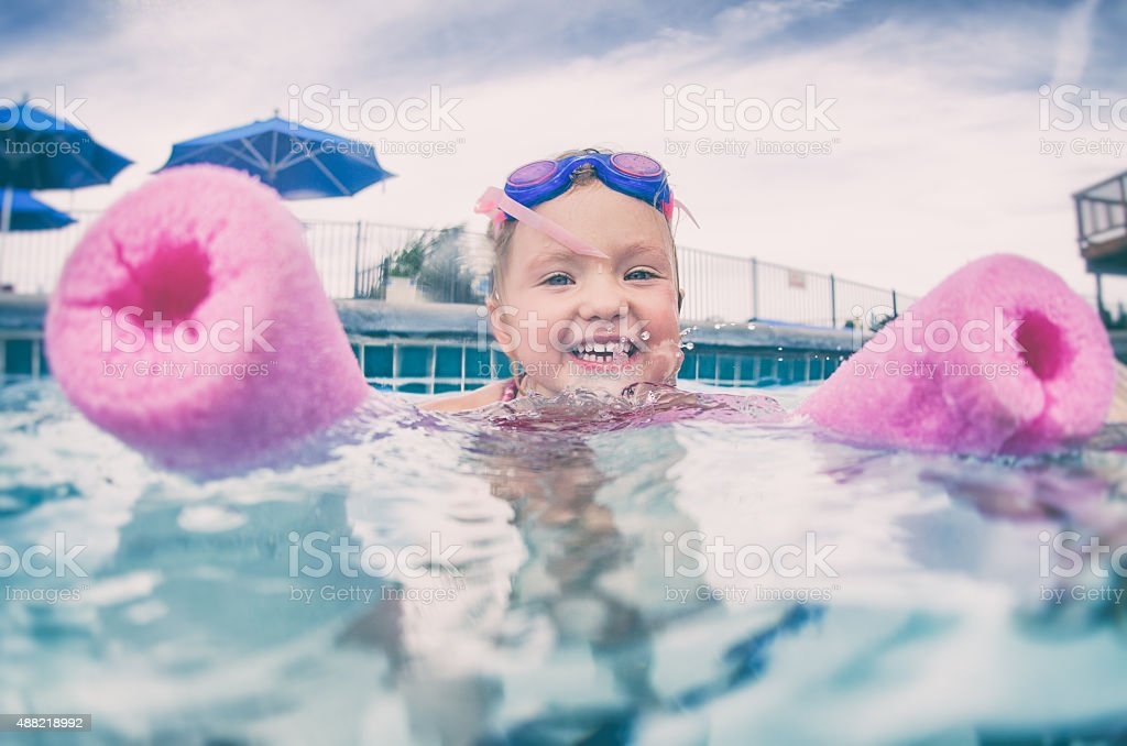 Little girl floats on the water with a swim noodle stock photo