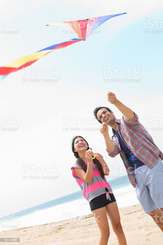 Little girl flying kite on the beach with her dad royalty-free stock photo
