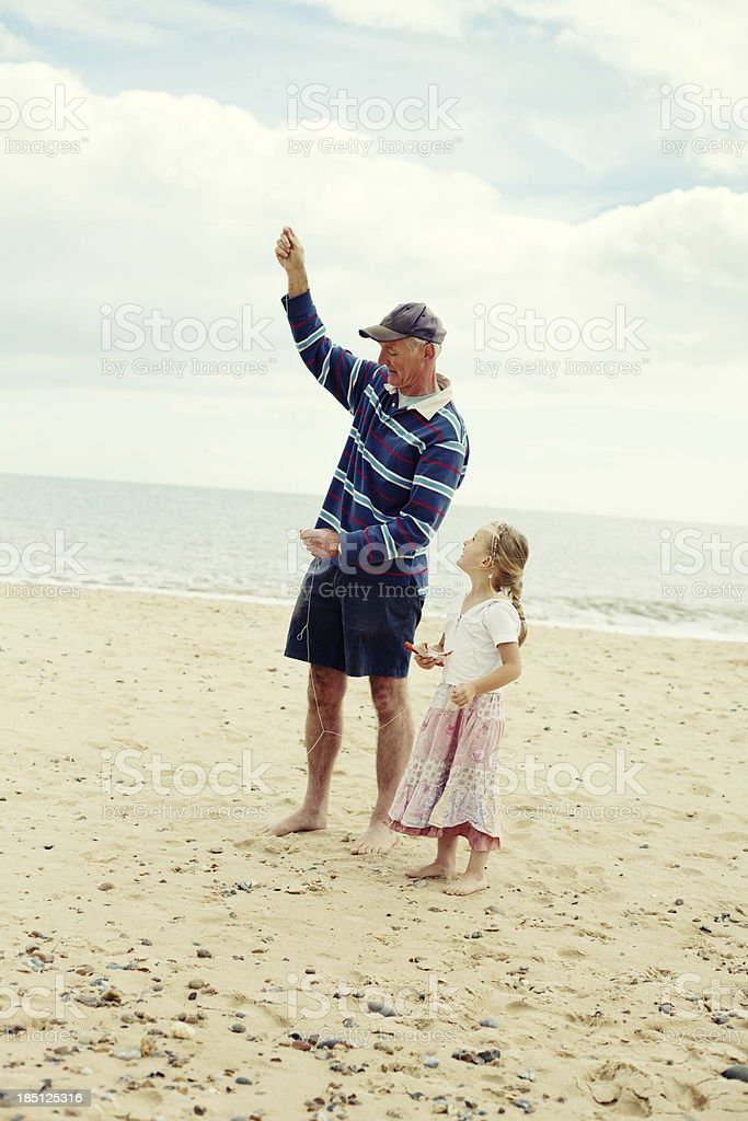 Little Girl Flying Kite with Grandad on Beach royalty-free stock photo