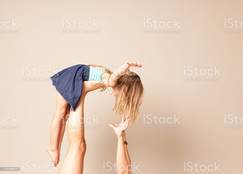 Little Girl 'Flying' on her parents feet stock photo