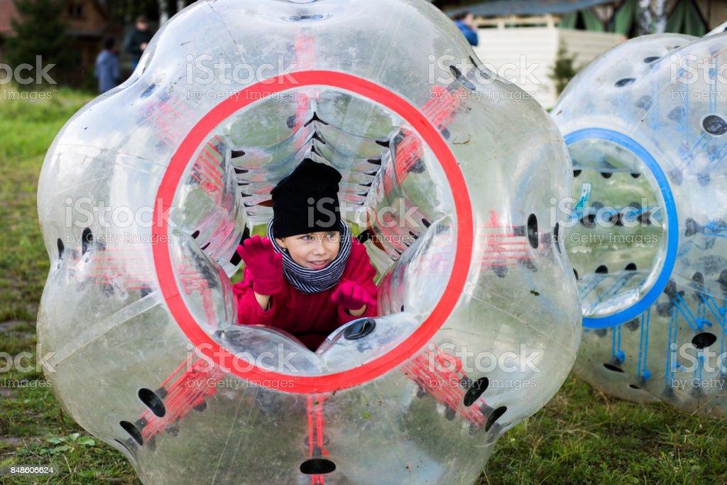 Little girl fun plays bumperball outdoors stock photo