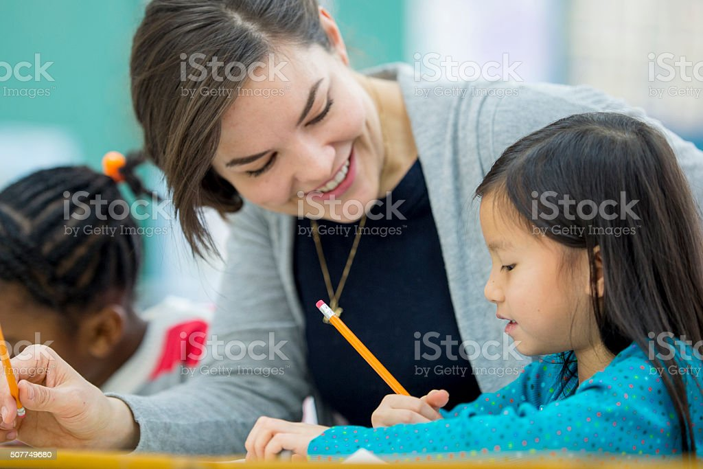 Little Girl Getting Help from Her Teacher stock photo