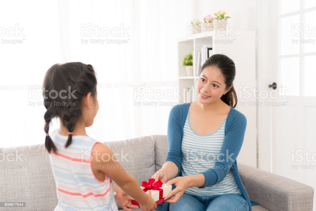 little girl give her young mother a red gift box stock photo