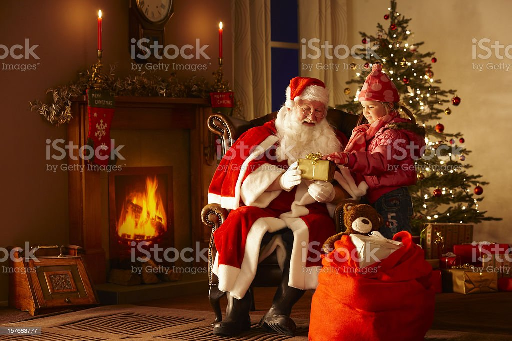 Little girl giving gift to Father Christmas in grotto stock photo