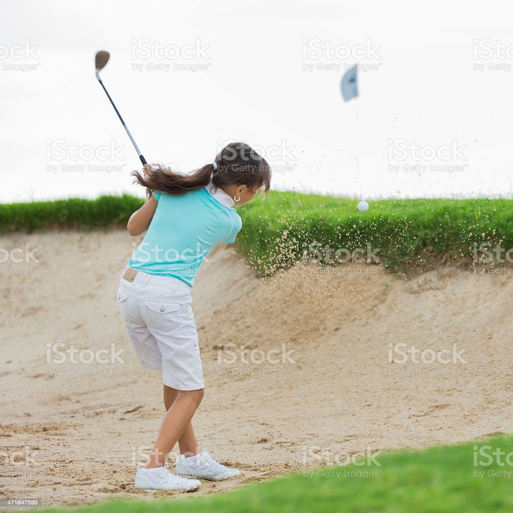 Little girl golfer hitting golf ball out of sand trap royalty-free stock photo
