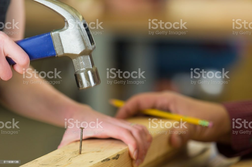 Little girl hammering nail into board while working with dad stock photo