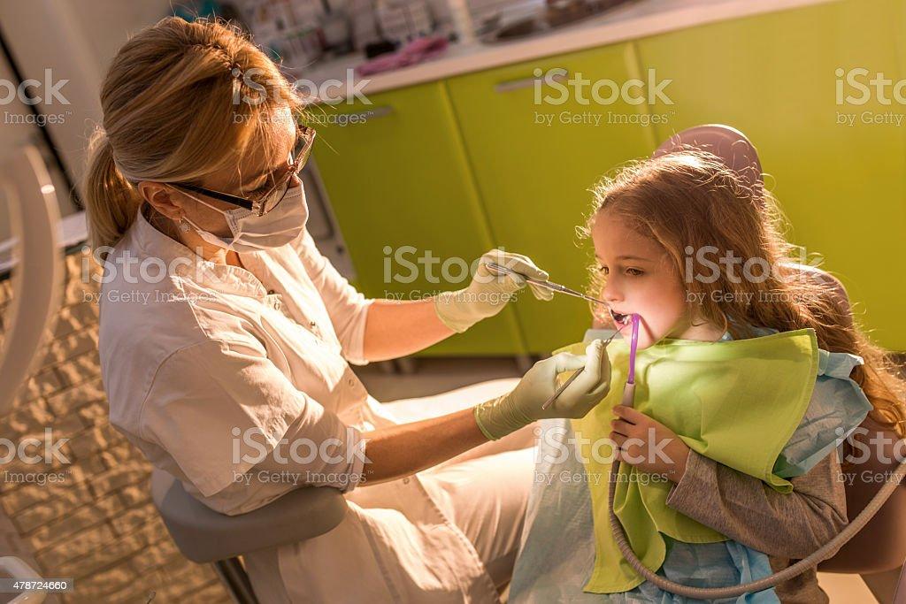 Little girl having dental procedure at female dentist. stock photo