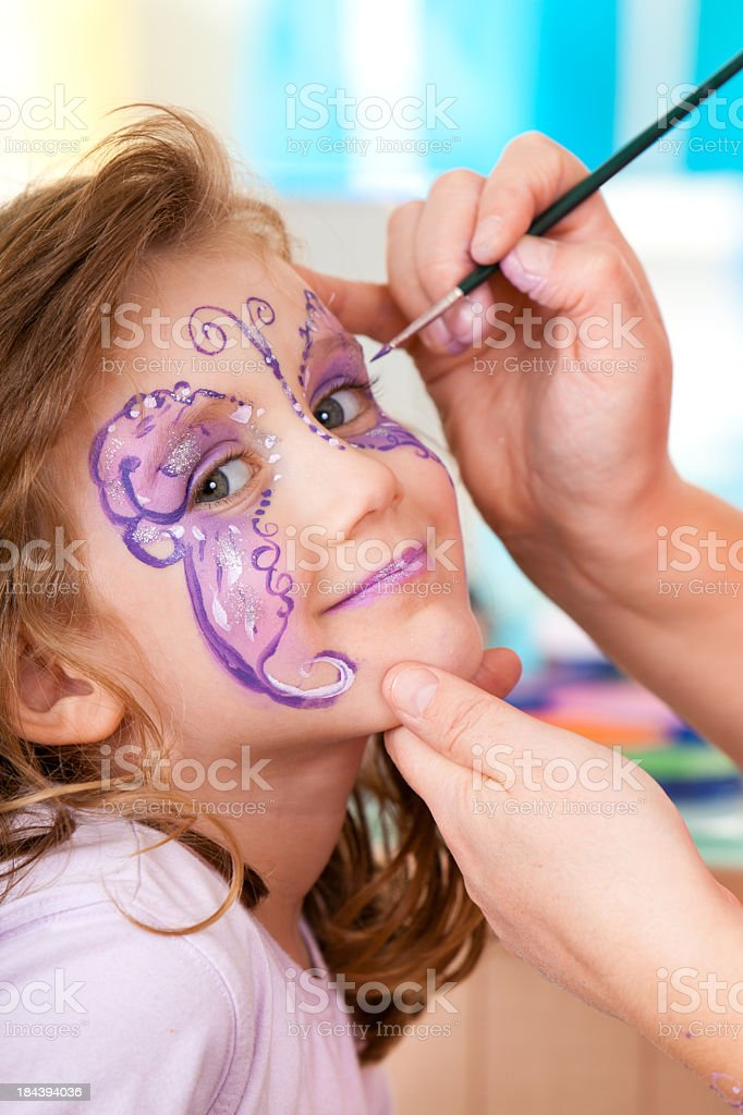 Little girl having face painted on birthday party stock photo