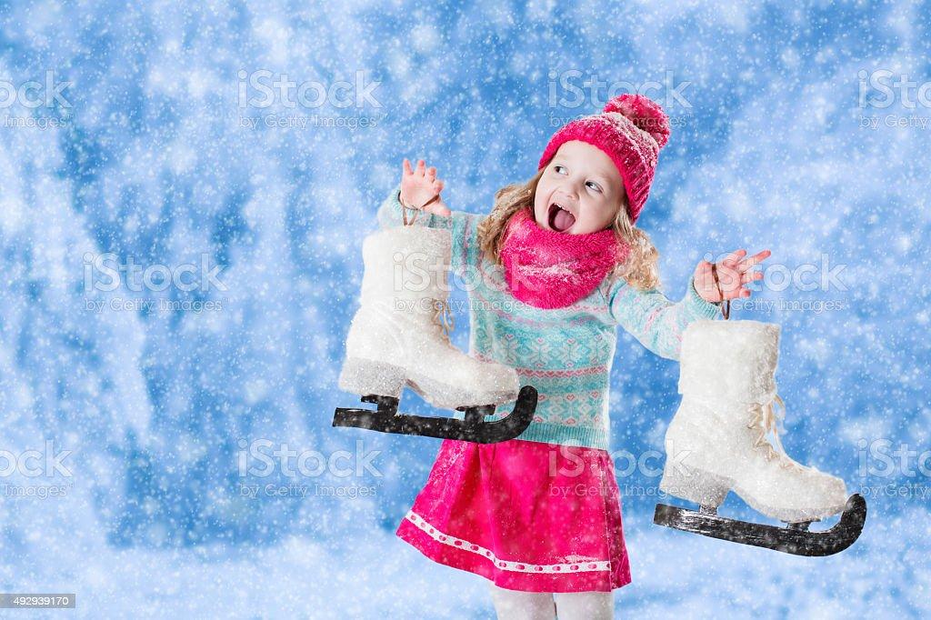 Little girl having fun at ice skating in winter stock photo