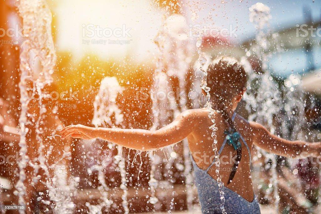 Little girl having fun in water park fountain stock photo