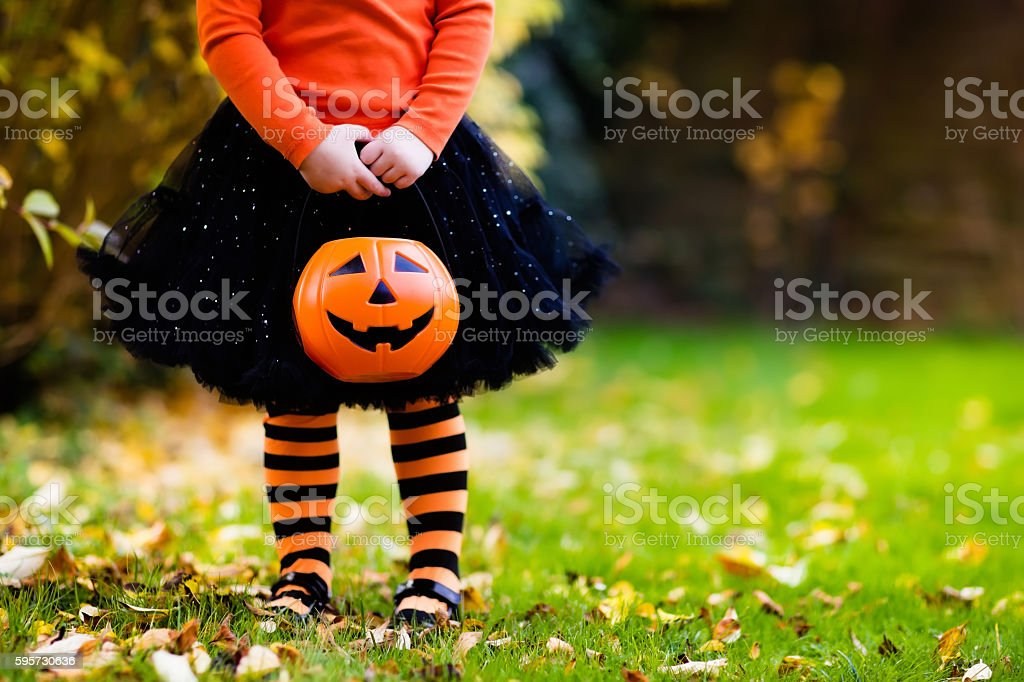 Little girl having fun on Halloween trick or treat stock photo