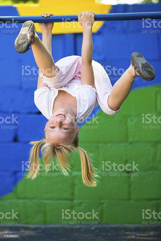 Little girl having fun on playground gymnastics bar stock photo