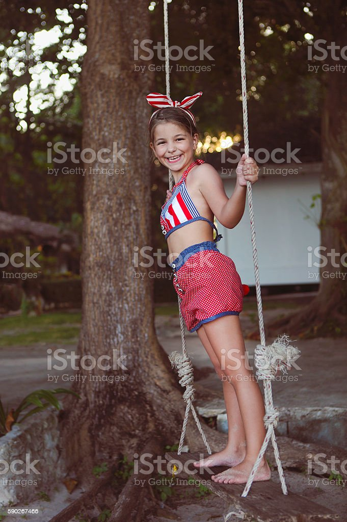 Little girl having fun on tire swing in summer day stock photo