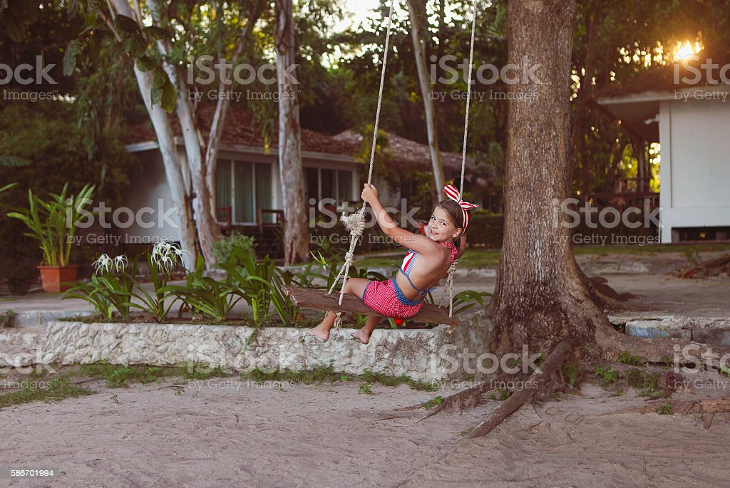 Little girl having fun on tire swing summer day stock photo