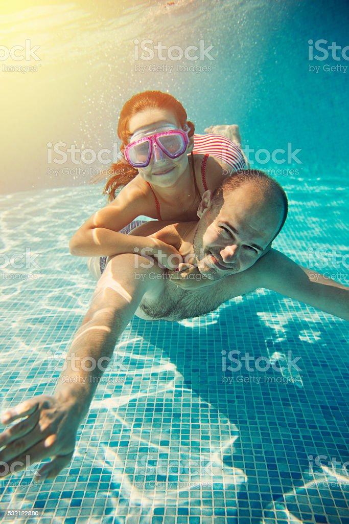 Little girl having fun riding underwater stock photo