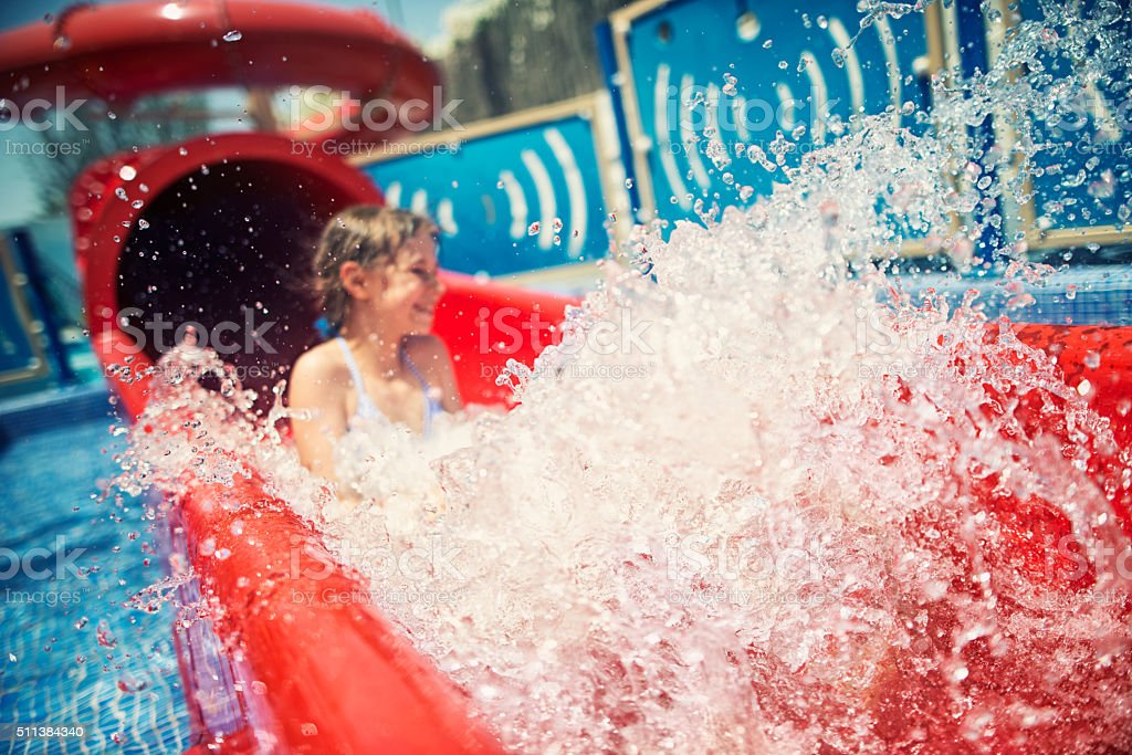 Little girl having fun sliding in water park stock photo