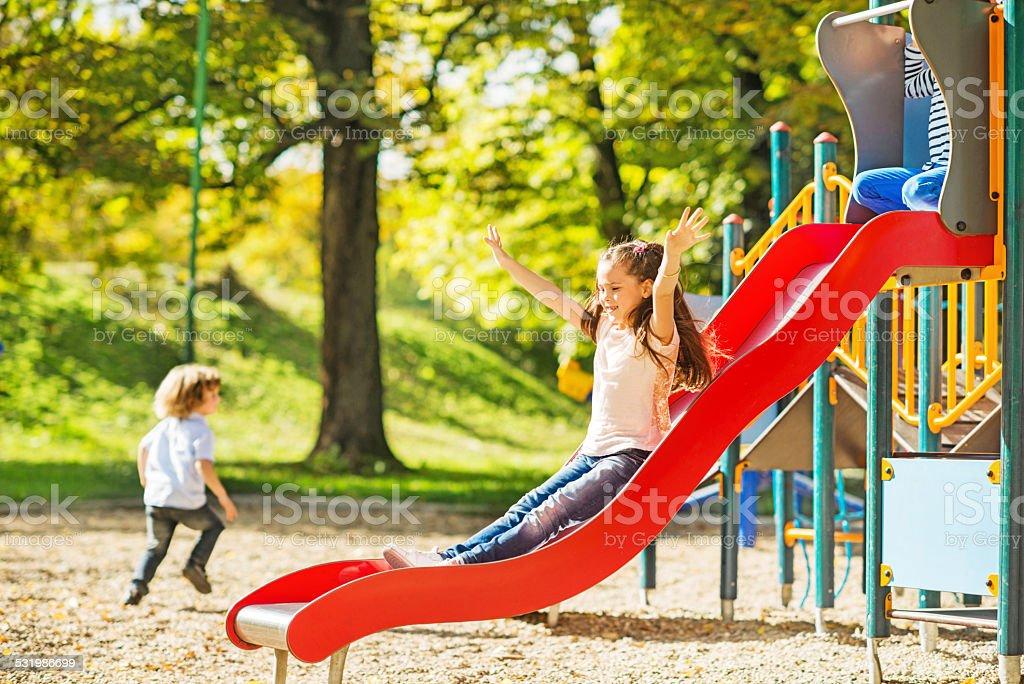 Little girl having fun while sliding. stock photo