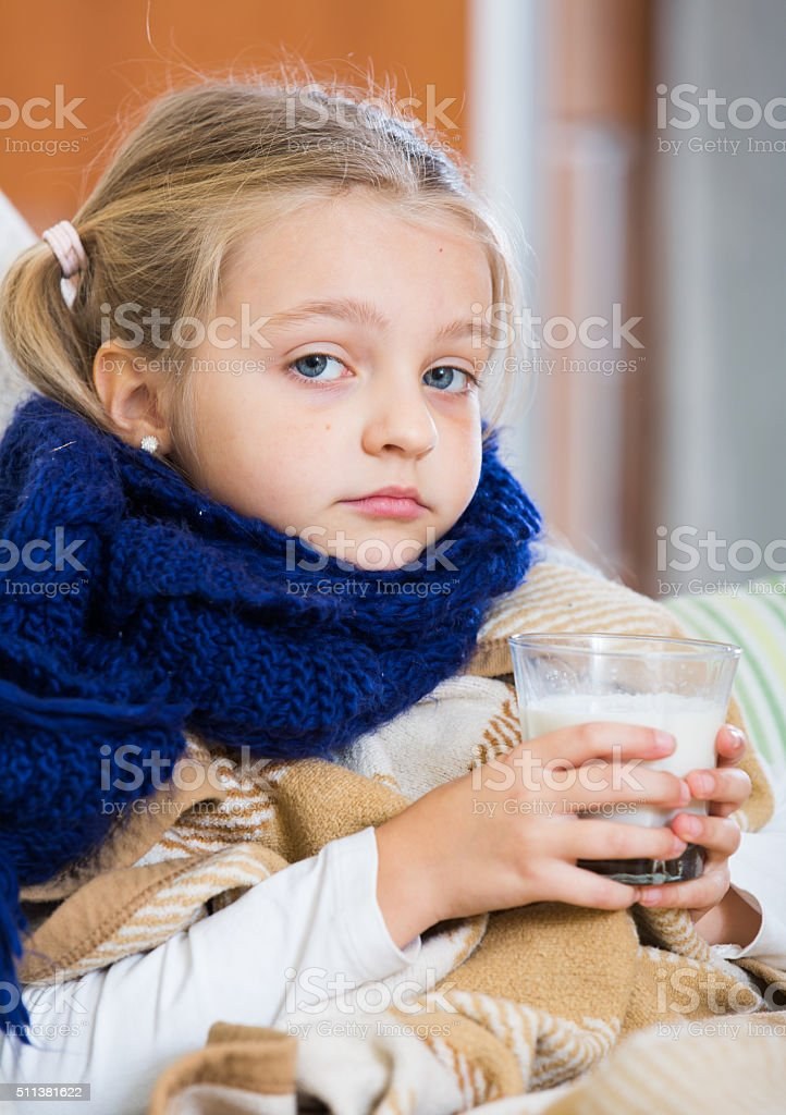 Little girl having heavy quinsy in domestic interior stock photo