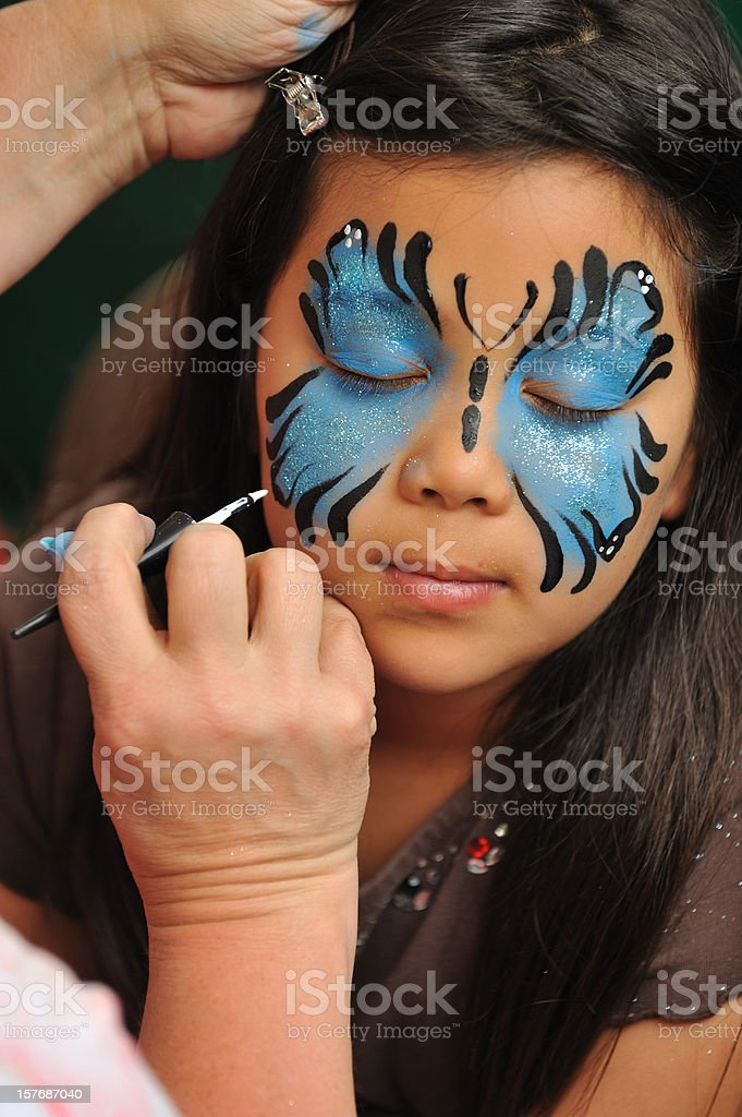 Little girl having her face painted. royalty-free stock photo