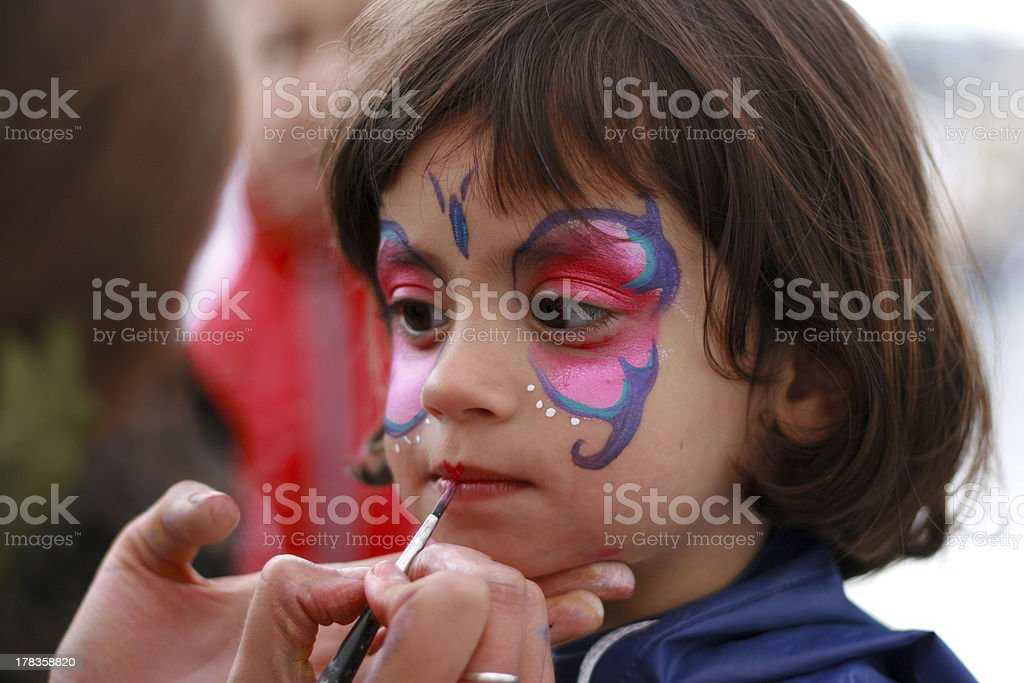 Little girl having her face painted stock photo