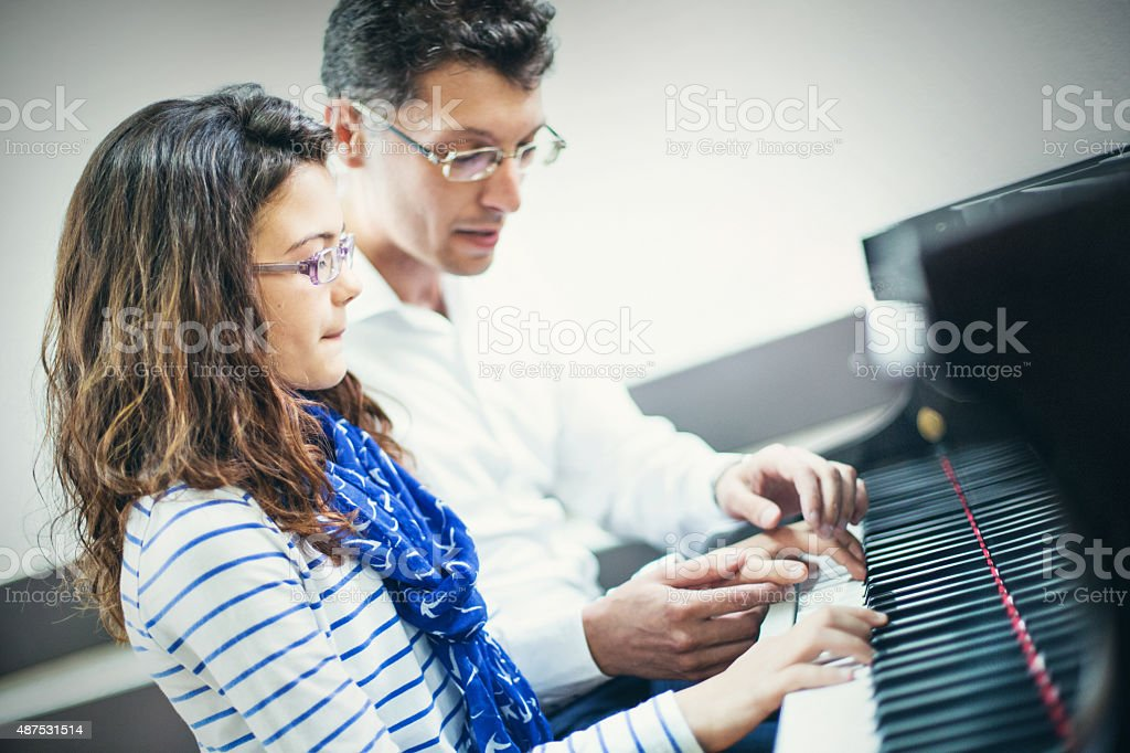 Little girl having piano class with her teacher. stock photo