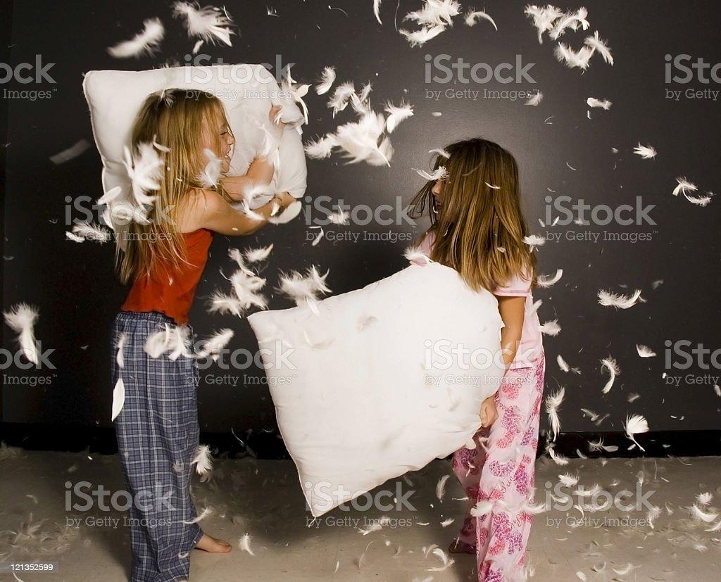 Little girl having pillow fight stock photo