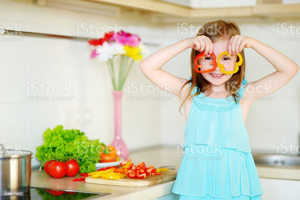 Little girl helping her mother in a kitchen stock photo