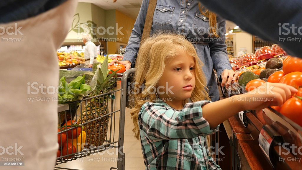 Little girl helping her mother shop in grocery store stock photo