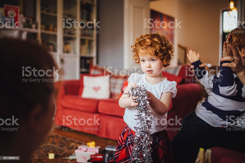 Little Girl Helping her Mother with the Christmas Decorations stock photo